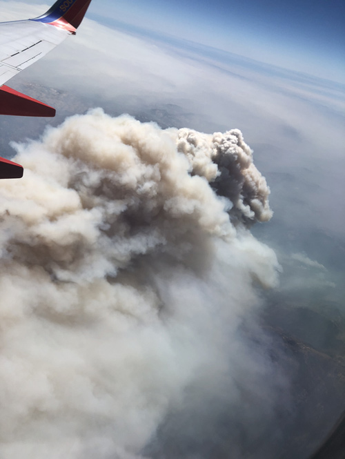 Large plume of smoke seen from an airplane, with airplane wing in view.